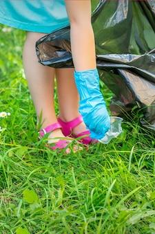 La mano del bambino pulisce il parco dagli utensili di plastica nell'erba nel parco