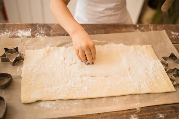 La mano di un bambino taglia la pasta con stampi di pan di zenzero sul tavolo di legno