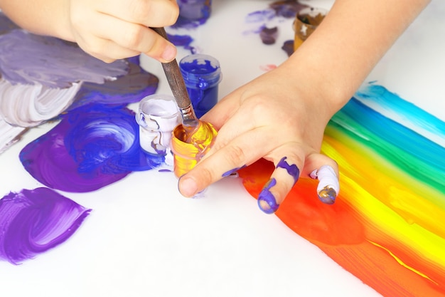 Colori della pittura di tiraggio della mano del bambino su un fondo bianco. creatività e hobby artistico