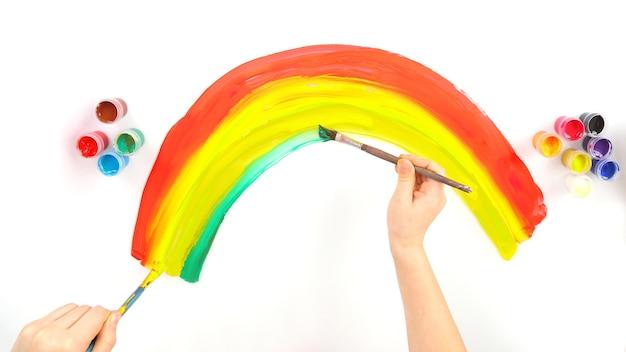 La mano del bambino disegna un arcobaleno su uno sfondo bianco. lavoro creativo