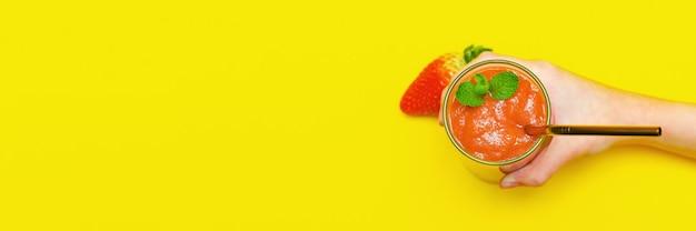 La mano del bambino tiene un frullato con fragole e un tubo da cocktail in metallo in un bicchiere di vetro, su uno sfondo giallo con spazio copia.vista dall'alto