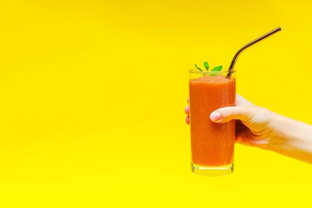 La mano del bambino tiene un frullato con fragole e un tubo da cocktail in metallo in un bicchiere di vetro, su uno sfondo giallo con spazio per le copie