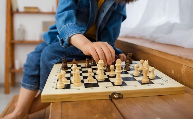 La mano del bambino sta giocando a scacchi sulla scacchiera nella stanza