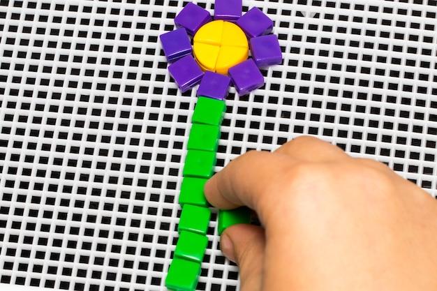La mano di un bambino mette un mosaico di fiori.