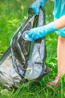 La mano del bambino mette i detriti di plastica nel sacco della spazzatura nel parco