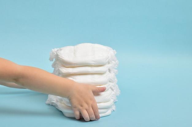 La mano di un bambino prende un pannolino mutandine su sfondo blu.