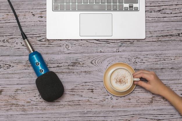La mano di un bambino con una tazza di caffè con crema e un microfono con un computer portatile su un tavolo di legno. pausa durante il lavoro.
