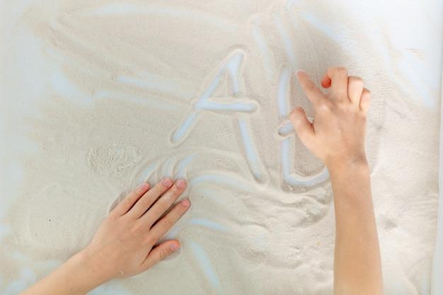 Mani del bambino che disegnano lettere nella sabbia