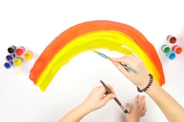 Le mani del bambino disegnano un arcobaleno su uno sfondo bianco. creatività e hobby dei bambini