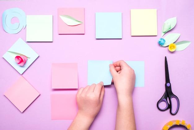 Le mani del bambino incollano adesivi per la preparazione di fiori da carta colorata Foto Premium