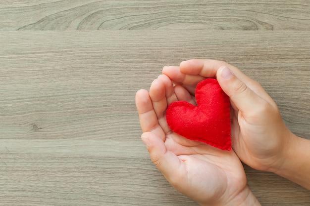 Mani del bambino che tengono un cuore fatto di feltro.