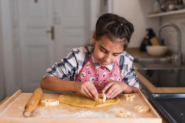 Mani del bambino che producono i biscotti dalla pasta cruda sotto forma di cuore, primi piani. il bambino prepara i biscotti e ritaglia delle figurine di pasta arrotolata a forma di cuore. avvicinamento.