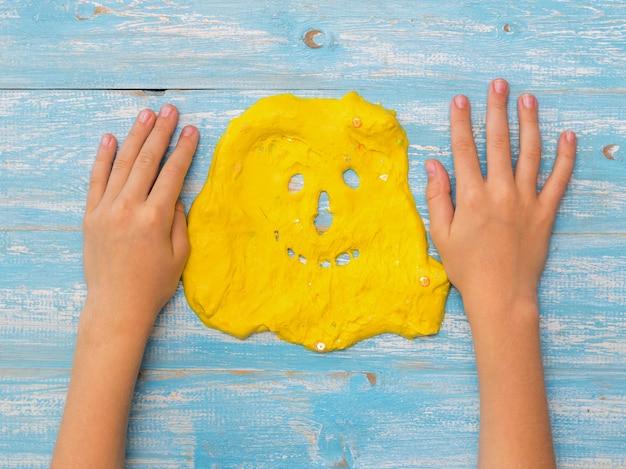 Le mani del bambino sul tavolo accanto alla faccia di una melma gialla. giocattolo antistress. giocattolo per lo sviluppo delle capacità motorie della mano.