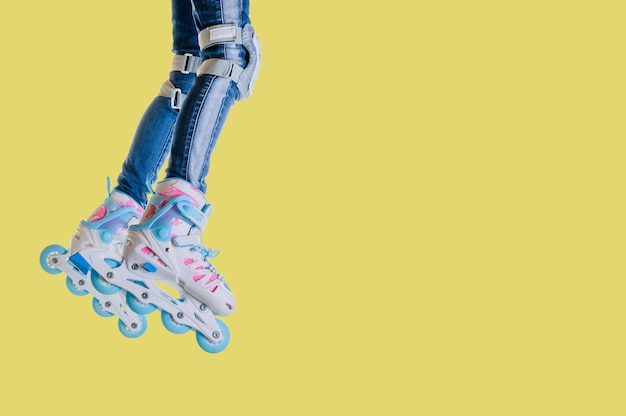 Gambe del bambino in jeans e pattini a rotelle su uno sfondo giallo. spazio per il testo. tempo libero e sport.