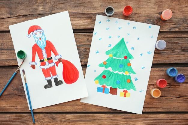 Dipinti per bambini di albero di natale con regali e babbo natale sul tavolo