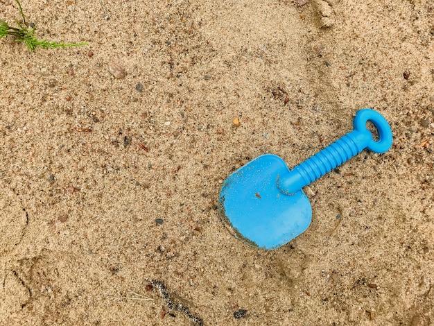 La scapola del bambino sulla sabbia bagnata. lama blu in sabbia sulla spiaggia. pala giocattolo abbandonata e dimenticata. concetto di ricreazione estiva per bambini dopo la quarantena. sabbia di consistenza. posto per un'iscrizione o un logo