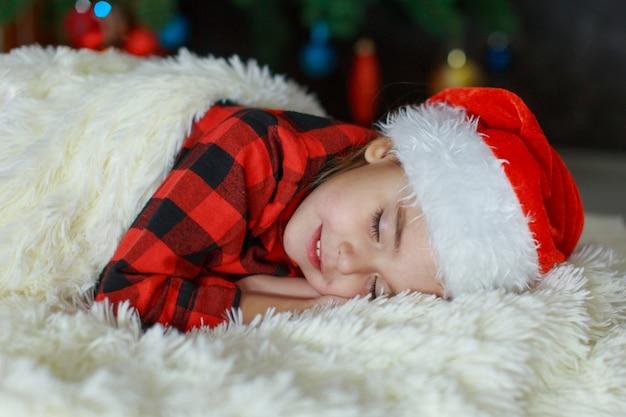 Un bambino con un cappello da babbo natale dorme capodanno.
