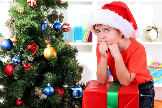Bambino con cappello da babbo natale vicino all'albero di natale con un grande regalo