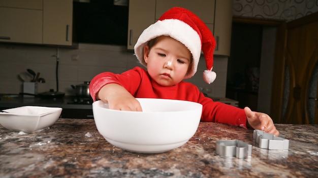 Bambino in un cappello da babbo natale che prepara una cena di capodanno