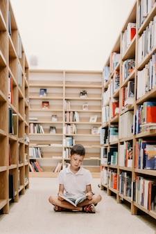 Bambino nella biblioteca scolastica. i bambini leggono libri. ragazzino che legge e studia. bambini al negozio di libri. bambino prescolare intelligente intelligente che sceglie libri da prendere in prestito.
