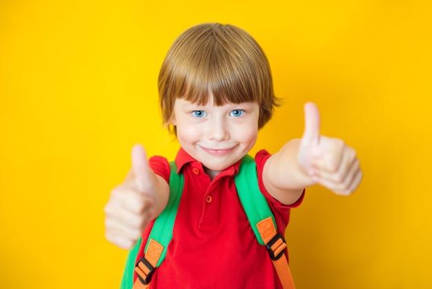 L'allievo del ragazzo dello scolaro del bambino mostra i pollici in su