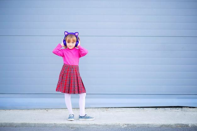 Un bambino, uno scolaro, ascolta musica in cuffie luminose wireless. cuffie bluetooth moderne