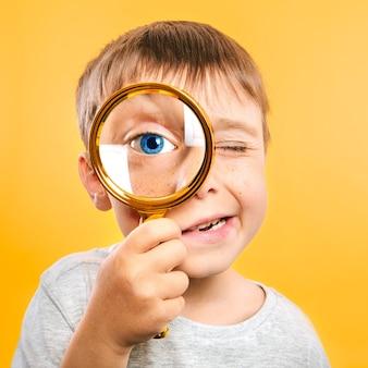 Il bambino vede attraverso la lente d'ingrandimento sulle superfici di colore giallo. occhio da bambino grande