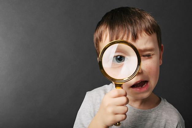Un bambino vede attraverso la lente d'ingrandimento