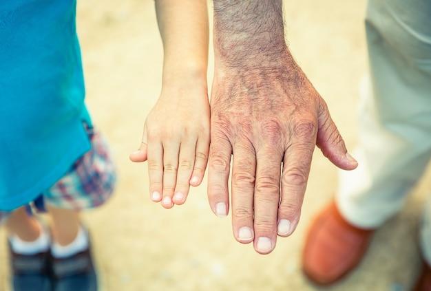 Bambino e uomo anziano che confrontano le dimensioni delle sue mani su uno sfondo di un percorso naturalistico. due diverse generazioni concetto.
