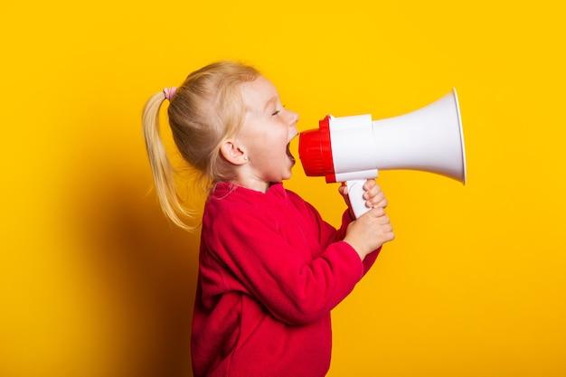Il bambino grida in un megafono bianco su uno sfondo giallo brillante