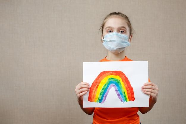 Un bambino mostra un disegno di un arcobaleno durante la quarantena coronavirus pandemica. resta a casa campagna di social media per la prevenzione del coronavirus, stiamo tutti bene, speriamo durante il concetto di pandemia di coronavirus