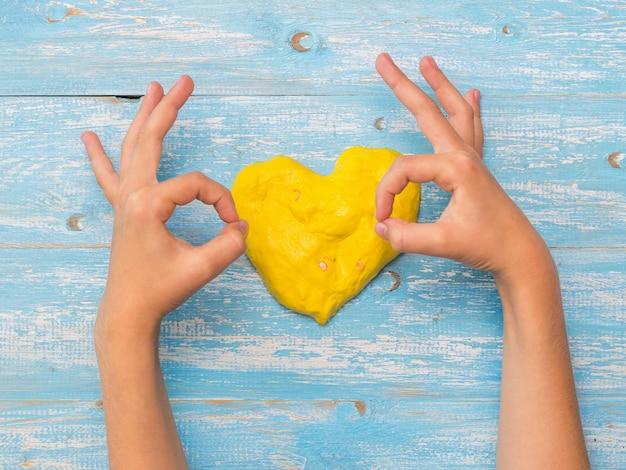 Il bambino mostra il gesto giusto sopra il cuore giallo. giocattolo antistress. giocattolo per lo sviluppo delle capacità motorie della mano.
