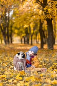 Un bambino si siede in foglie gialle cadute con un carlino nel parco autunnale. amici fin dall'infanzia.