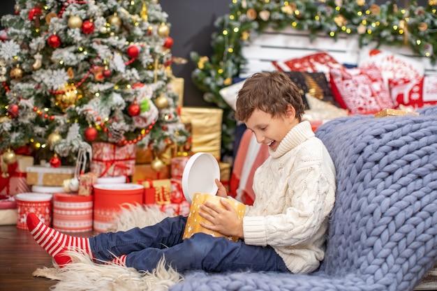 Il bambino si siede in camera vicino al letto con un albero di natale e apre il regalo ricevuto da babbo natale