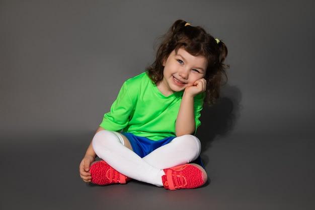 Il bambino si siede a gambe incrociate, appoggiandosi la testa con la mano. uniforme sportiva da calcio. concetto di classe di calcio per ragazze