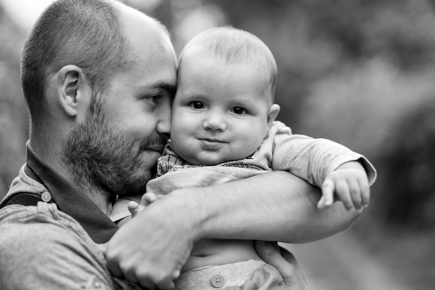 Il bambino si siede sulla spalla del papà e sorride. una foto in bianco e nero