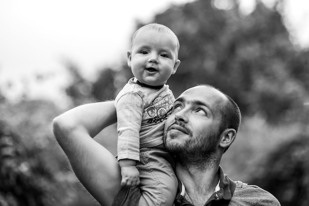 Il bambino si siede sulla spalla del papà e sorride. bianco e nero
