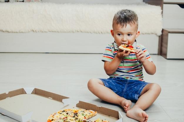 Il bambino si siede per terra e mangia la pizza molto appetitosa e golosa, in pantaloncini e maglietta