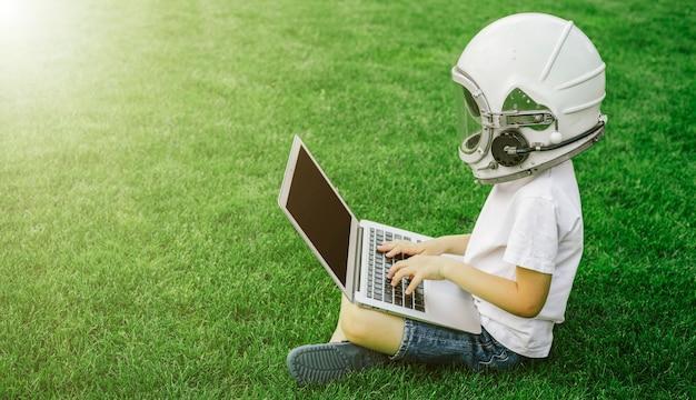Un bambino si siede sull'erba nel casco di un astronauta e studia su un laptop online godendosi la natura.