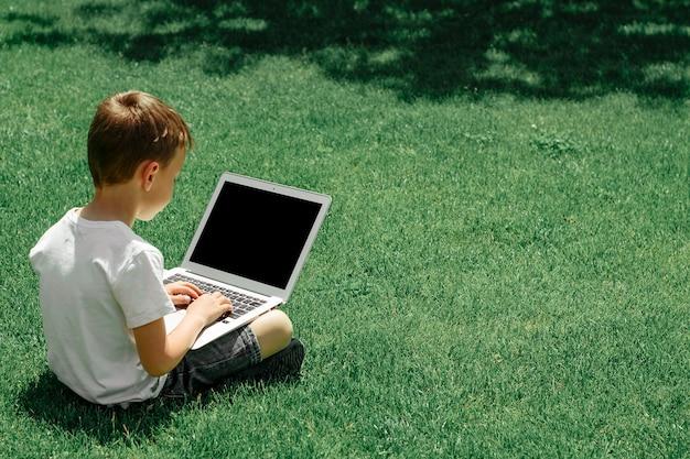Un bambino si siede sull'erba e studia con un laptop online, godendosi la natura