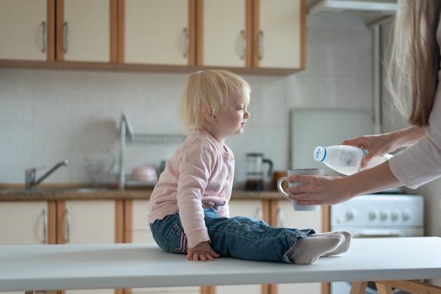Il bambino si siede in cucina e aspetta che la mamma versi il latte nella tazza.