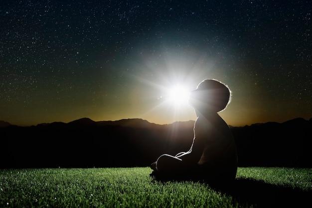 Un bambino si siede sulla cima di una montagna al tramonto e sogna