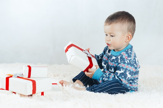 Il bambino, seduto sul letto e gioca con i regali confezionati, capodanno in un maglione di renne