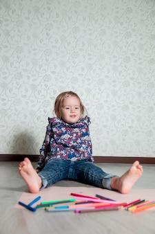Bambino seduto sul pavimento vicino a pastelli e carta. bambina disegno, pittura. concetto di creatività. felice, sorridente.