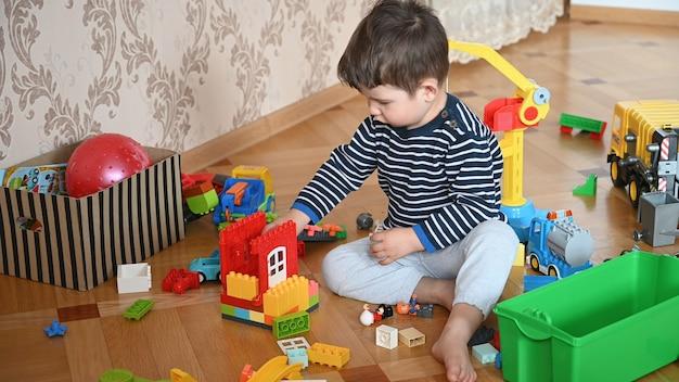 Il bambino seduto sul pavimento gioca il costruttore.