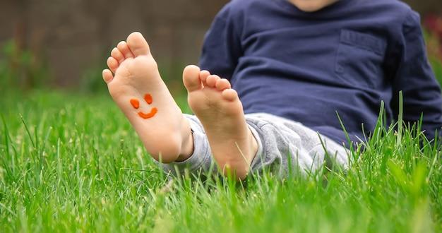 Bambino seduto sull'erba, sorridente sulla gamba del bambino con la vernice