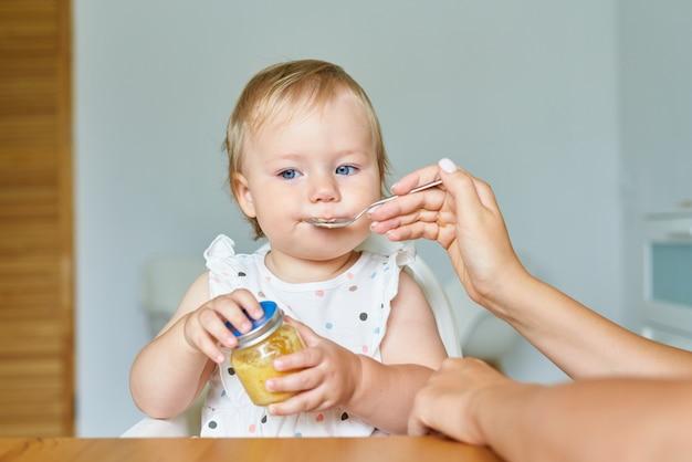 Bambino seduto sul seggiolone mentre la mamma dà il cibo dal barattolo al bambino a casa
