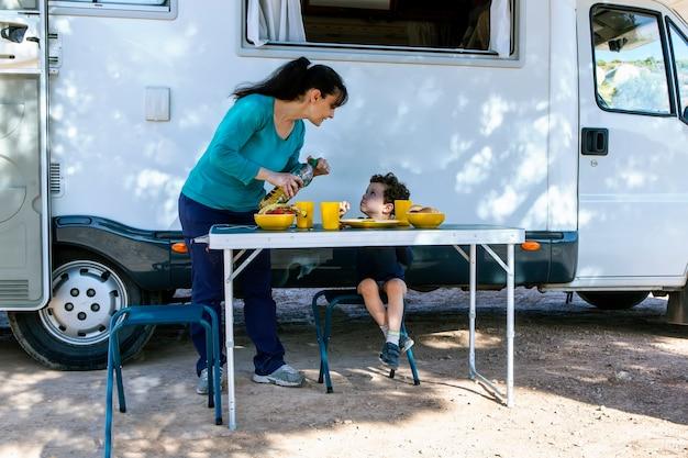 Bambino seduto al tavolo accanto al camper mentre sua madre serve spuntini in una giornata di campeggio