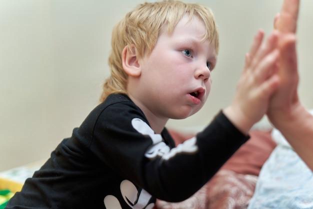 Un bambino in costume da scheletro si siede sul divano con un'emozione sul viso