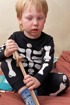 Un bambino in costume da scheletro con una spada di legno si siede sul divano